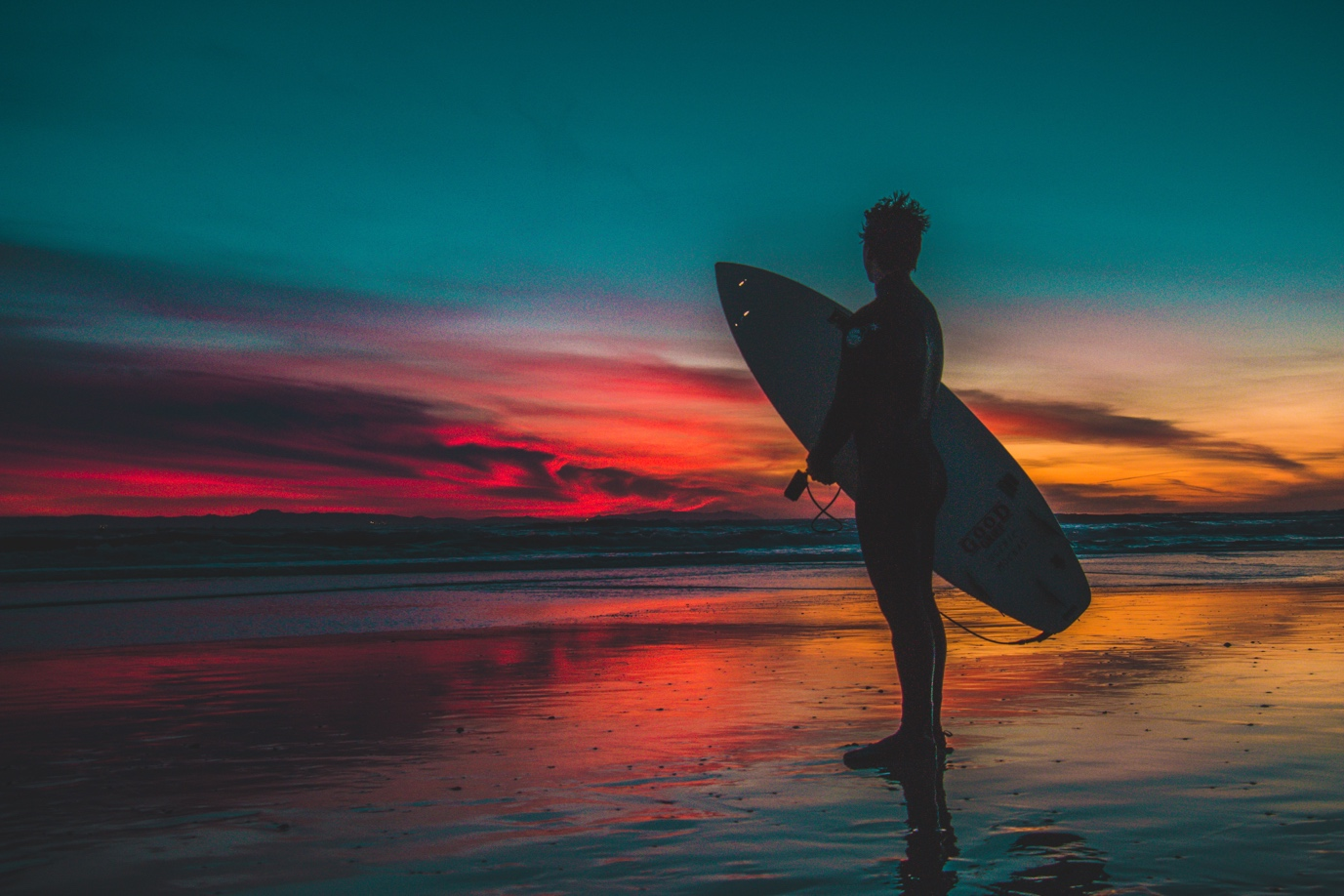 A person carrying a surf board walking on a beach  Description automatically generated